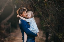 A little girl cuddles her daddy during their photography session