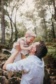 A baby girl holds her daddy's face as he hoists her above him