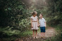 A brother and sister hold hands amongst the greenery on a dirt track