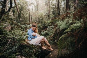 A mother breastfeeds her baby in a lush green forest