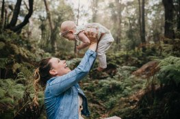 A mother laughs with her baby in a lush green forest