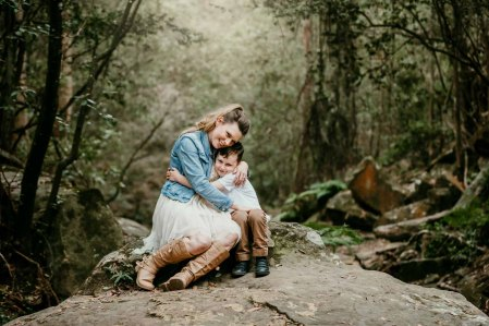 A mother embraces her son in amongst a green rainforest