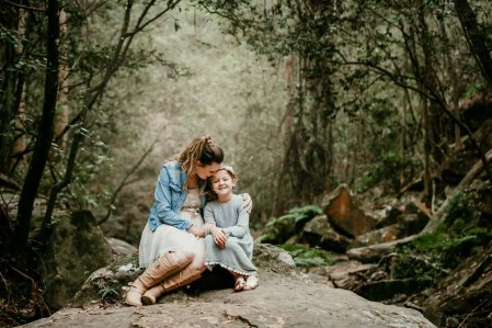 A mother cuddles her daughter in amongst a green rainforest