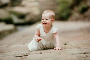 A baby girl crawls along a path and giggles at the camera