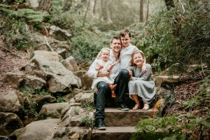 3 children sit with their father sandstone steps in a forrest
