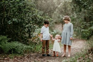 Siblings hold their baby sisters hands during a photo session