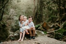 3 little siblings snuggle together in a lush green forest