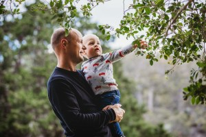 A little boy reaches for green leaves while he's held by his father