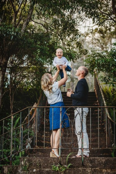 Parents laugh with their little boy as he is hoisted high above them