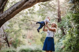 A mother hoists her little boy above her as they laugh together