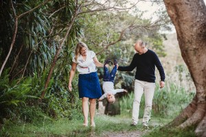Two parents carry their little boy by the feet as he laughs