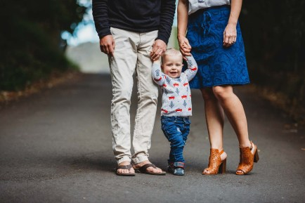 A little boy stands between his parents holding both their hands