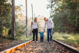 Parents stand on train tracks with their little boy as he giggles