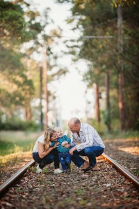 Parents cuddle their little boy as they stand on abandoned train tracks