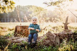 A little boy sits on an old log with the golden sunset behind him