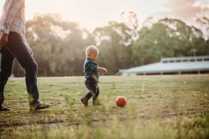 A little boy kicks a ball around on the grass at sunset