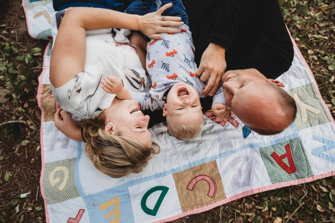 A little boy lays between his parents laughing as they tickle him